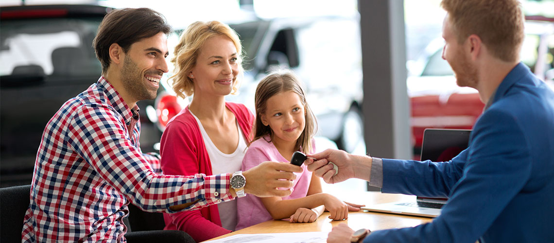 Happy family at car dealership